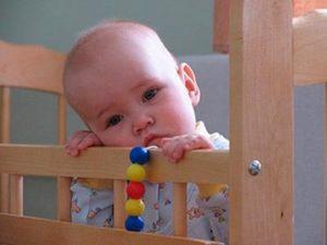 Ребенок в детской кроватке