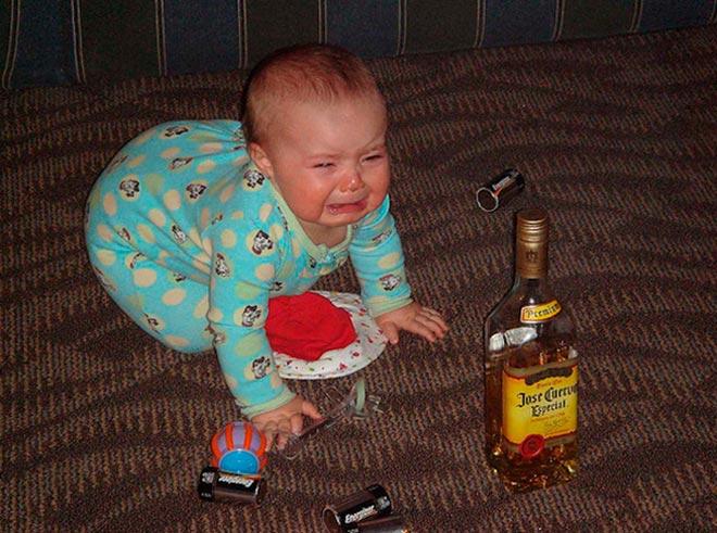 Плачущий ребенок рядом с бутылкой алкоголя