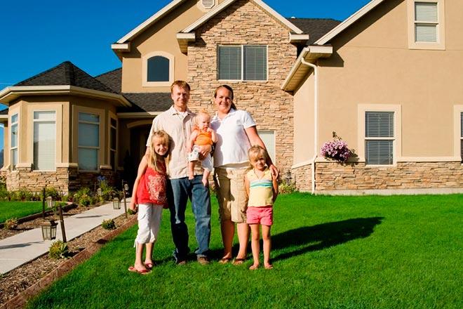 Семья на лужайке на фоне домика