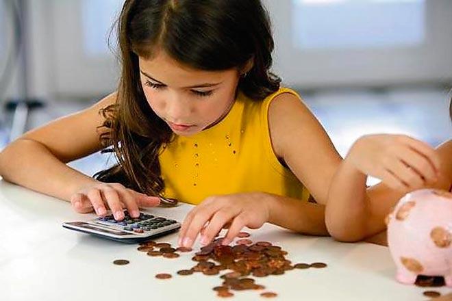 Девочка считает деньги на калькуляторе