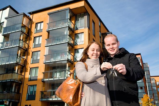 Молодая пара на фоне дома держат ключи