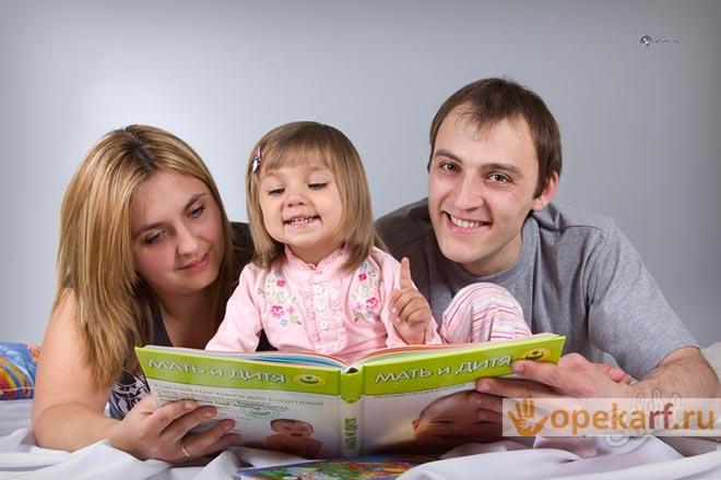 Ребёнок с родителями читает книгу