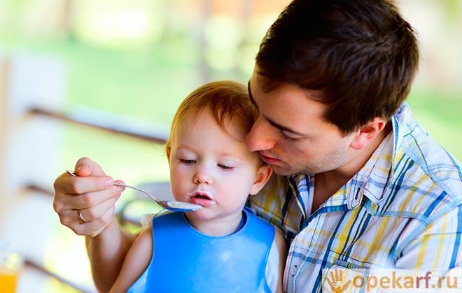 Папа кормит ребенка с ложки