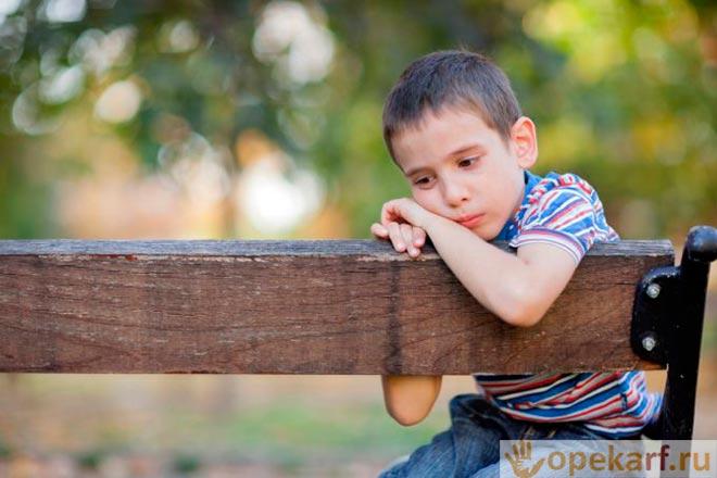 Подросток сидит на скамейке