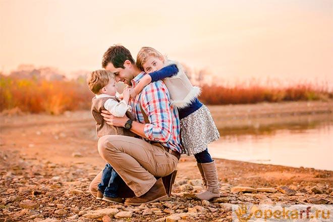 Папа с детьми на берегу реки