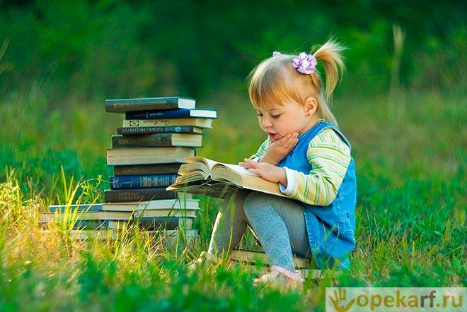Девочка читает книги в поле